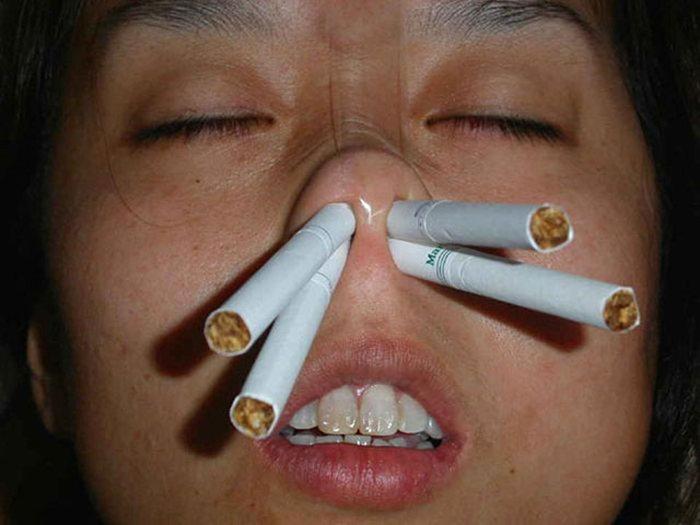 Burnuna sigara sokmuş insan